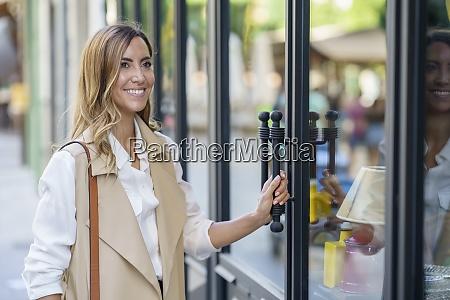 smiling woman standing at store door