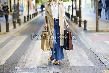 woman carrying bag while walking on