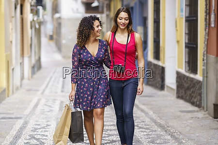 smiling lesbian couple with shopping bag