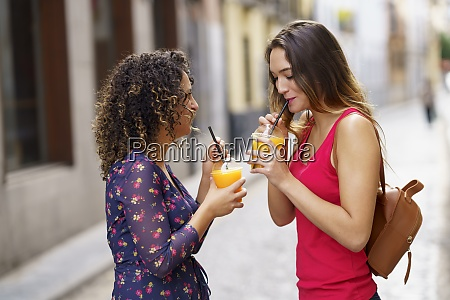 women drinking juice while standing on