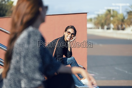smiling young woman looking at friend