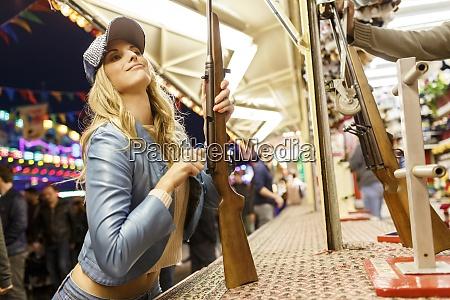 young woman at fun fair shooting