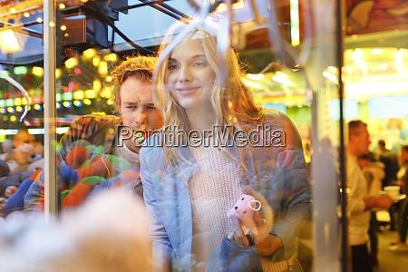 young couple at fun fair looking
