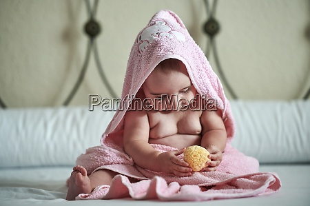 baby girl in pink towel playing