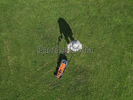 woman with lawn mower standing in