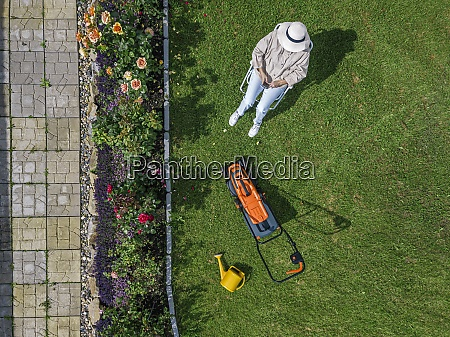 woman with lawn mower sitting on