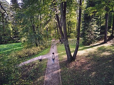 woman walking on footpath in park