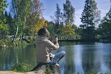 woman photographing through smart phone while