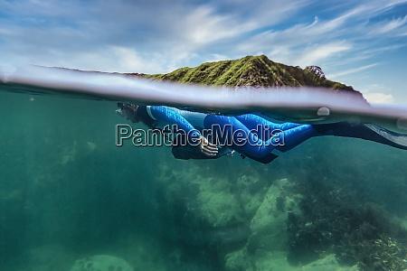 woman in diving suit diving undersea
