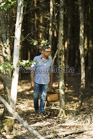mature man standing while holding basket