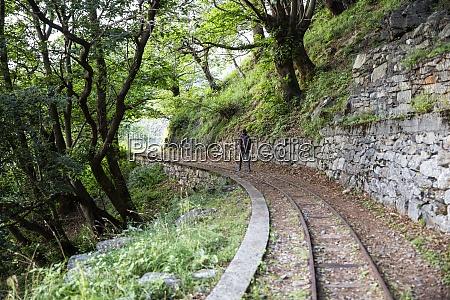 man hiking along tracciolino railroad track