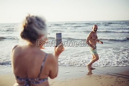 woman taking photo of man running