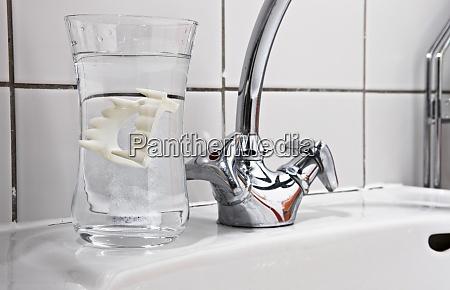vampire dentures in water glass on