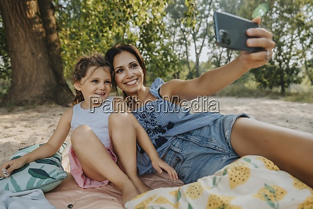 mother and daughter taking selfie on