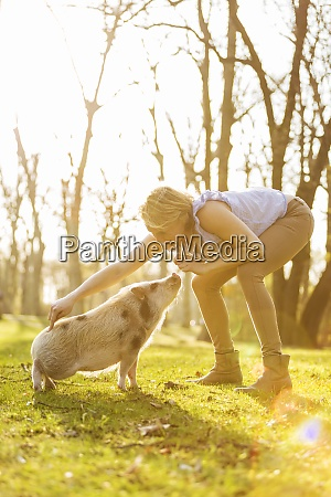 woman taming piglet in park