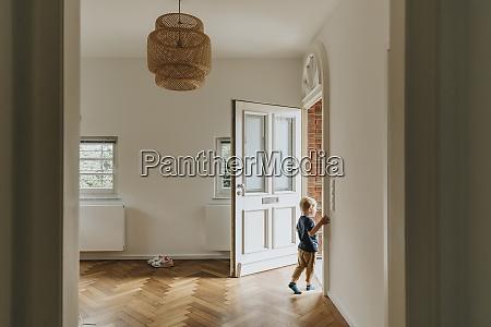boy standing by open door at