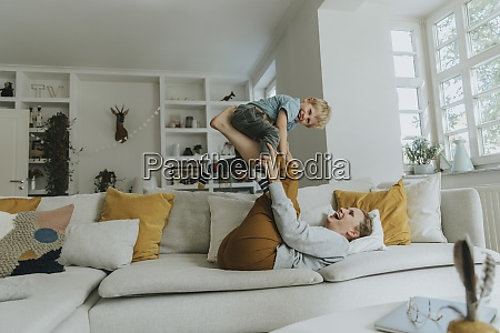mother picking son on leg while