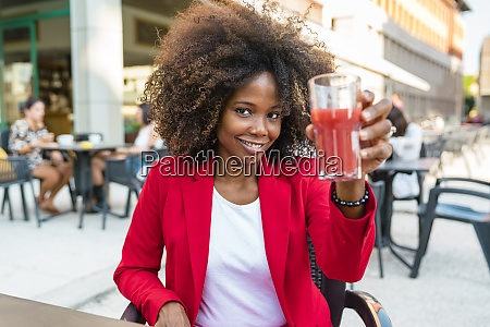 mid adult woman holding juice glass
