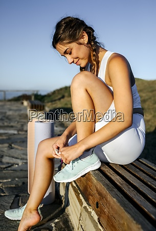 smiling young woman tying shoelace while