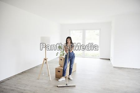 pregnant woman standing with mop at