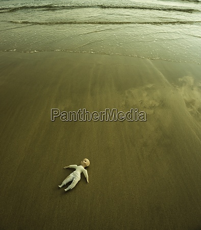 doll lying on wet sandy beach