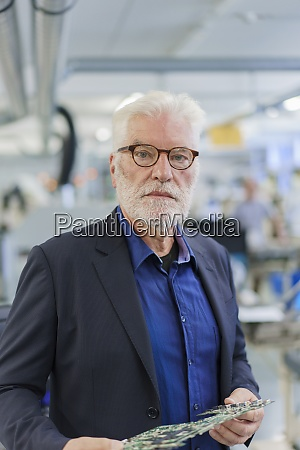 confident senior male manager holding machine
