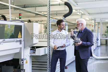 senior manager discussing machine part with