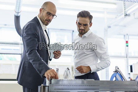 confident male professionals discussing over machinery