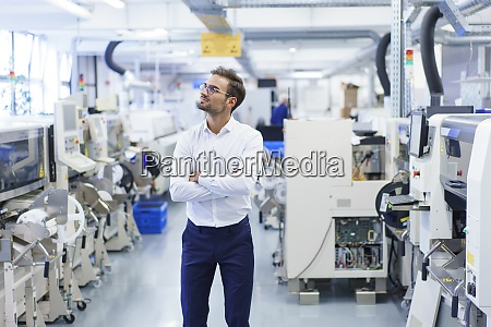 thoughtful young businessman standing with arms