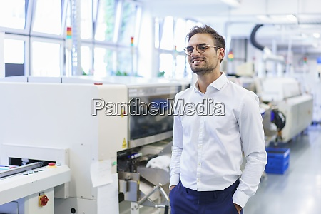 smiling young male technician standing with