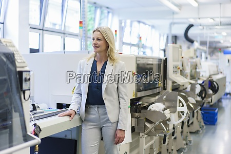 thoughtful mature blond businesswoman standing by