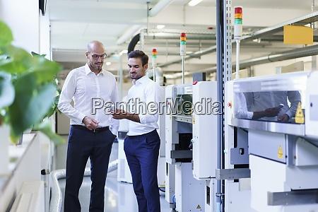 male technicians discussing over remote control