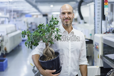 smiling confident businessman holding potted plant