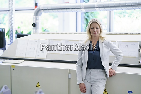 confident blond businesswoman standing against machinery
