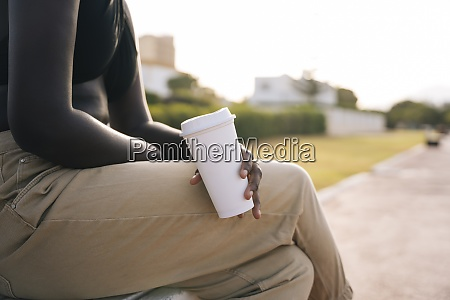 woman holding coffee cup while sitting