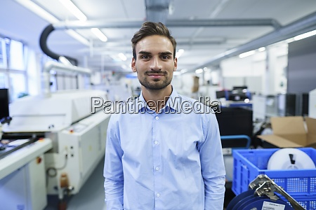 smiling young male professional standing at