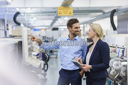 smiling male technician looking at businesswoman