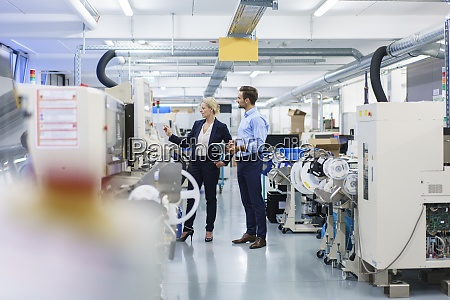 mature businesswoman discussing over machinery with