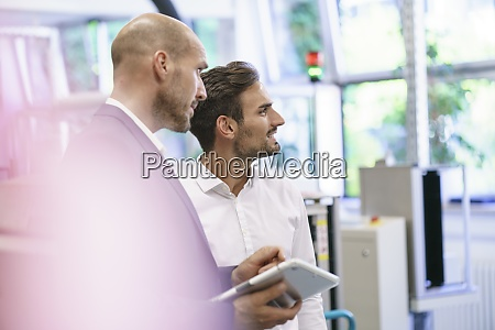 male professionals discussing while looking away