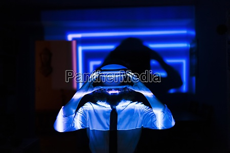 man holding virtual glasses while standing