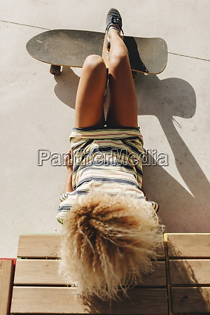 blond afro woman reclining with skateboard