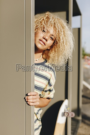 blond afro woman standing by metallic