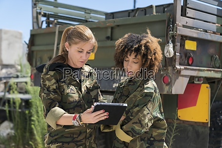 female military soldiers discussing over digital