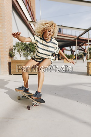 blond woman with arms outstretched skateboarding