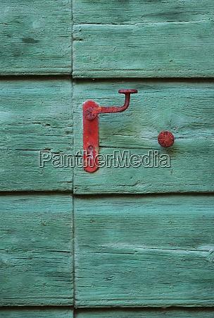 wooden door with red handle