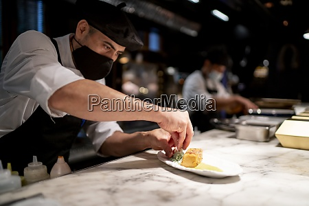 chef garnishing pudding while standing in