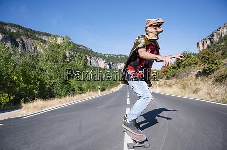 man wearing dinosaur mask skateboarding on