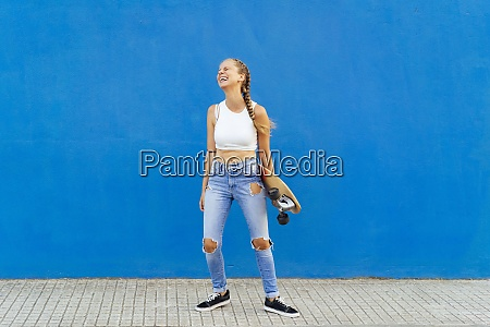 cheerful woman holding skateboard standing on