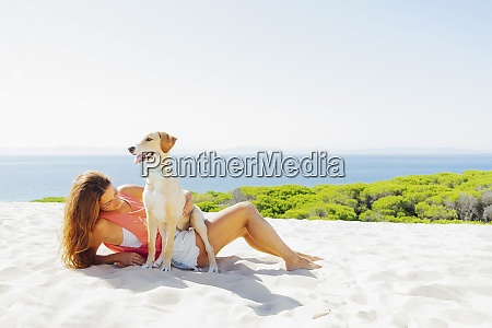 woman with dog relaxing at beach