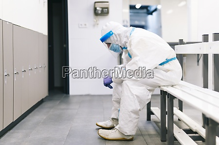 thoughtful man wearing protective suit sitting